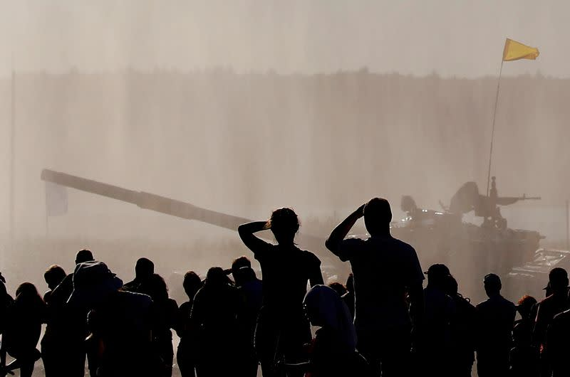 FILE PHOTO: People watch a T-72 B3 tank operated by a crew from Belarus during the Tank Biathlon competition at the International Army Games 2018 in Alabino