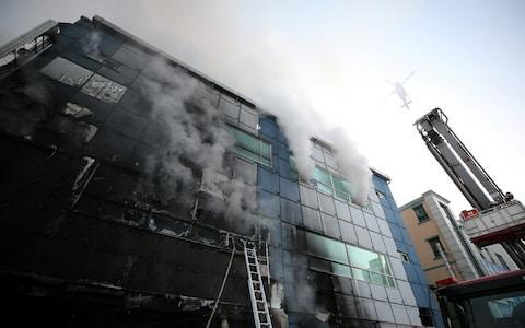 Smoke rises from a burning building in Jecheon, South Korea - Credit: YONHAP/REUTERS