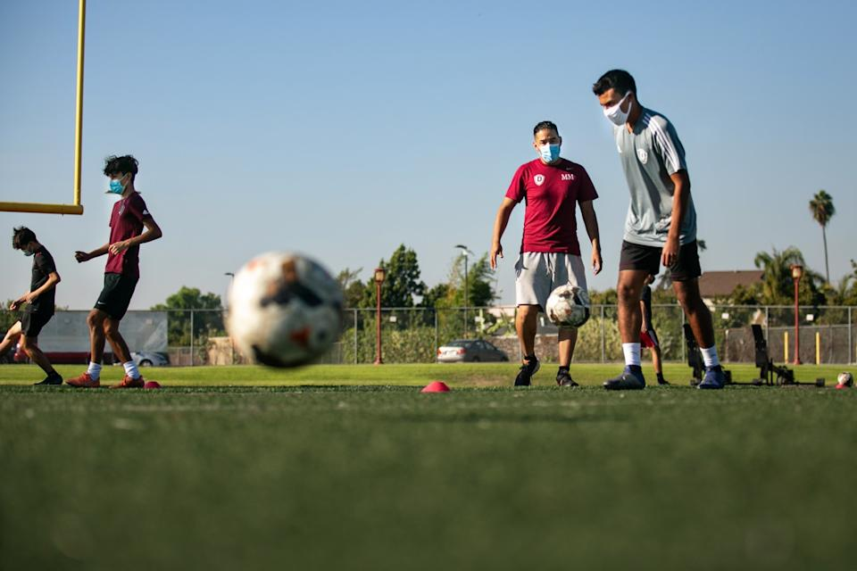 Downey High soccer coach Marvin Mires instructs his team during drills Oct. 30, 2020.