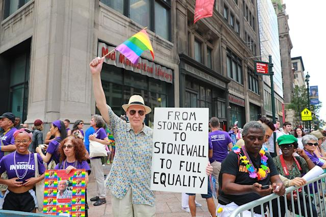 <p>A flag-bearing man holds up a sign during the N.Y.C. Pride Parade in New York on June 25, 2017. (Photo: Gordon Donovan/Yahoo News) </p>