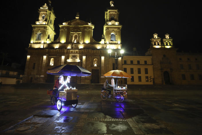 Street vendors leave Bolivar Square at the start of an official continuous multi-day curfew in an effort to contain the spread of new coronavirus infections, in Bogota, Colombia, Friday, Jan. 22, 2021. Colombia's capital city is reimposing lockdown measures as COVID-19 infections rise around the country. (AP Photo/Fernando Vergara)
