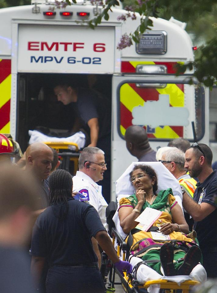 Authorities load a woman into a Mass Casualty ambulance after a floor collapsed on Thursday, June 26, 2014, in Katy, Texas. A floor collapsed under a large crowd of people gathered for a religious event at a home, sending three dozen people to hospitals, though most suffered minor injuries, authorities said. The collapse occurred while as many as 125 people gathered for the event in a residential neighborhood in Katy, just west of Houston. (AP Photo/Houston Chronicle, Cody Duty)