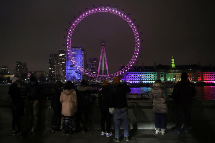 A small group of people look across from the embankment towards the London Eye ferris wheel by the River Thames in London, Thursday, Dec. 31, 2020. The London Eye is one of the traditional sites for New Year's Eve firework display, but it has been cancelled due to the ongoing coronavirus pandemic and the restrictions in place to try and stop its spread. (AP Photo/Matt Dunham)