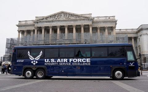 Air Force bus meant to transport Speaker of the Pelosi and other members of Congress to flight to Afghanistan sits in front of House of Representatives in Washington - Credit: Reuters