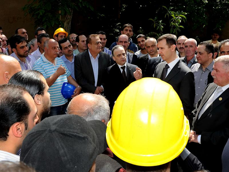 In this photo released by the Syrian official news agency SANA, President Bashar Assad, center right, visits the Umayyad Electrical Station on May Day, a day after a powerful bomb hit the capital. in Damascus, Syria, Wednesday, May 1, 2013. (AP Photo/SANA)