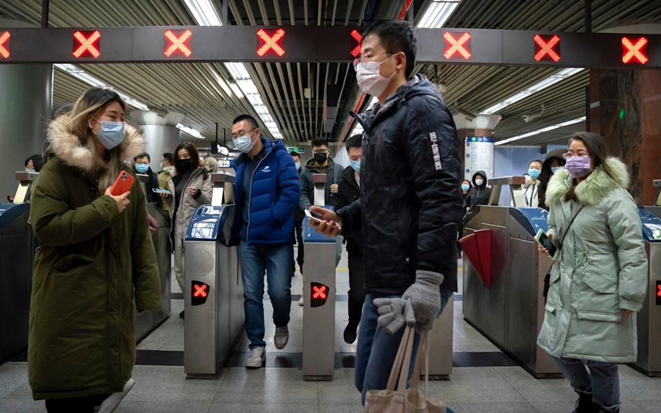 People wearing face masks to protect against the spread of the coronavirus walk through a subway station in Beijing - Mark Schiefelbein/AP