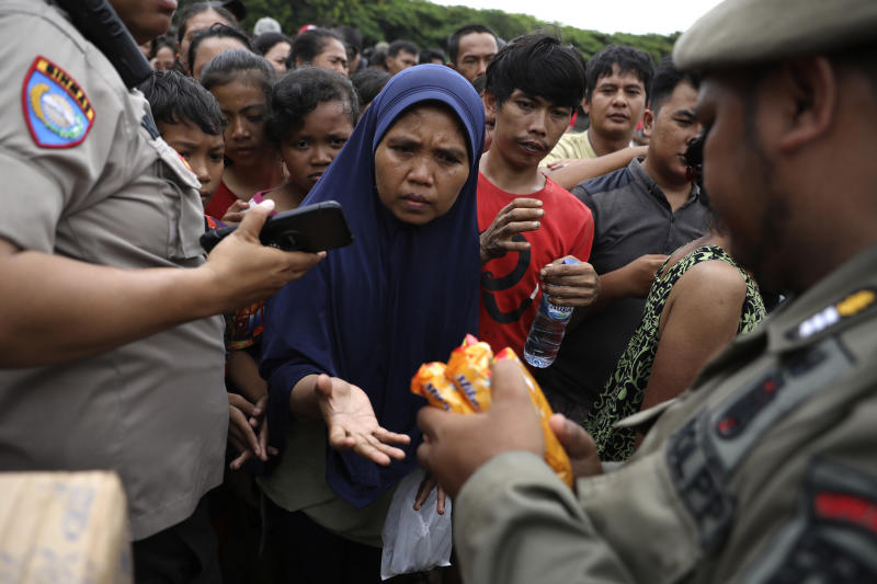 People queue up to receive food at an aid distribution point for those affected by the floods in Jakarta, Indonesia, Saturday, Jan. 4, 2020. Monsoon rains and rising rivers submerged parts of greater Jakarta and caused landslides in Bogor and Depok districts on the city's outskirts as well as in neighboring Lebak, which buried a number of people. (AP Photo/Dita Alangkara)