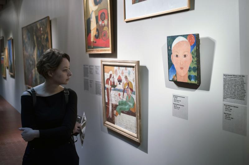 A visitor looks at Alexander Nikolayev's 'The Road of Life' on display at the exhibition of renowned avant-garde collection from the Savitsky State Art Museum of Karakalpakstan in Uzbekistan, opened in the Pushkin Fine Arts Museum in Moscow, Russia, Friday, April 7, 2017. More than 200 paintings from the Savitsky State Art Museum of Karakalpakstan went on display in Moscow, a rare traveling exhibit from the gallery widely regarded as having the world's second-best collection of Soviet avant-garde art. (AP Photo/Pavel Golovkin)