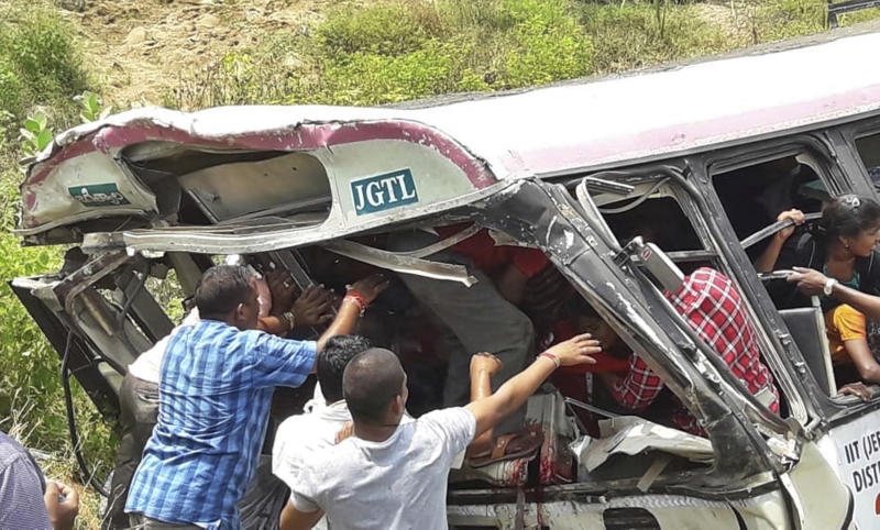 Rescuers reach for passengers from a bus that fell into a gorge in Jagtiyal district of Telangana, India, Tuesday, Sept. 11, 2018. A bus carrying pilgrims from a Hindu temple in the hills of south India plunged off a road Tuesday, killing more than 50 people including four children, officials said. (AP Photo)