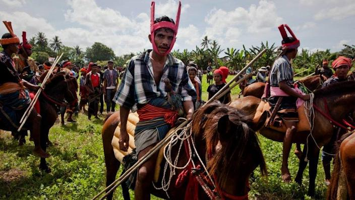 Sumbanese men riding their horse as attending Pasola festival - an animist religion is widely practised on the island