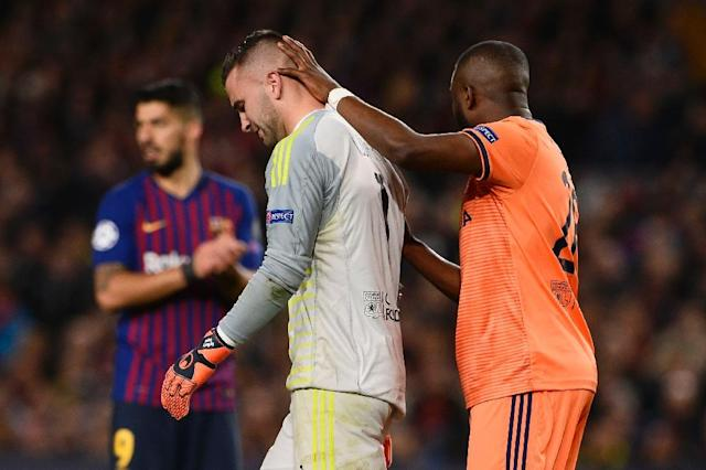 Lyon goalkeeper Anthony Lopes is consoled by one of his teammates as he leaves the field injured and in tears (AFP Photo/Josep LAGO)