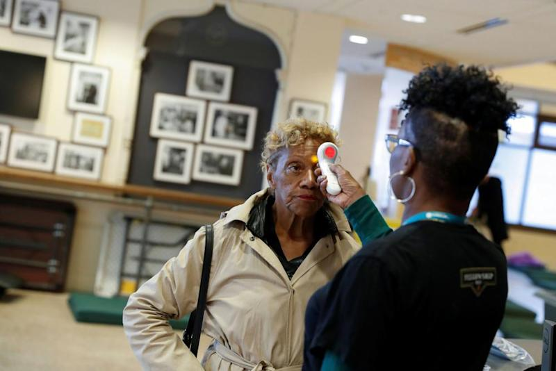 Ruth Cowan, 71, has her temperature taken upon entering St Anthony's winter shelter in San Francisco.