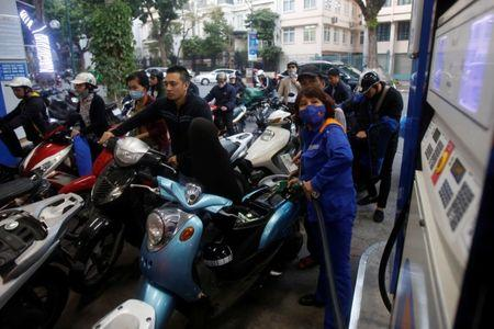 An employee pumps petrol for clients at a petrol station in Hanoi