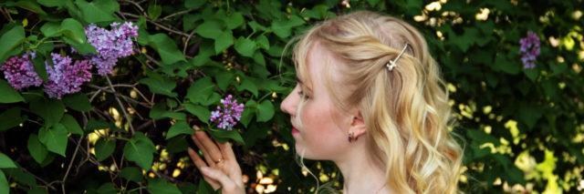 Woman admires lilac flowers.