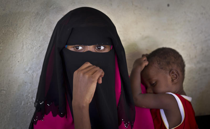 A Somali mother and her baby wait in line to receive a five-in-one vaccine against several potentially fatal childhood diseases, at the Medina Maternal Child Health center in Mogadishu, Somalia Wednesday, April 24, 2013. On the eve of the Global Vaccine Summit in Abu Dhabi and coinciding with World Immunization Week, the authorities in Somalia, which has one of the lowest immunization rates in the world, launched the new deployment of a pentavalent vaccine against diphtheria, tetanus, whooping cough, hepatitis B, and haemophilus influenzae type B the bacteria that causes meningitis and pneumonia. (AP Photo/Ben Curtis)