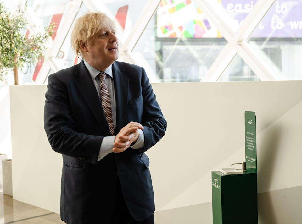 Britain's Prime Minister Boris Johnson uses a hand sanitising station as he visits a Marks & Spencer clothing department store in Westfield shopping centre in east London on June 14, 2020 to see the coronavirus measures in place in advance of the reopening tomorrow. - A variety of English shops and some outdoor attractions are set to open tomorrow for the first time in nearly three months, as Britain continues to ease its coronavirus lockdown. (Photo by John NGUYEN / POOL / AFP) (Photo by JOHN NGUYEN/POOL/AFP via Getty Images)