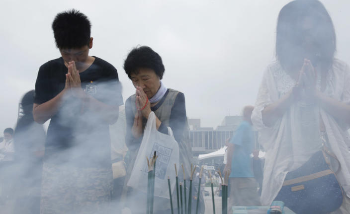 People pray for the atomic bomb victims at the Hiroshima Peace Memorial Park in Hiroshima, western Japan, Tuesday, Aug. 6, 2013. Japan marked the 68th anniversary Tuesday of the atomic bombing of Hiroshima with pledges to seek to eliminate nuclear weapons. (AP Photo/Shizuo Kambayashi)