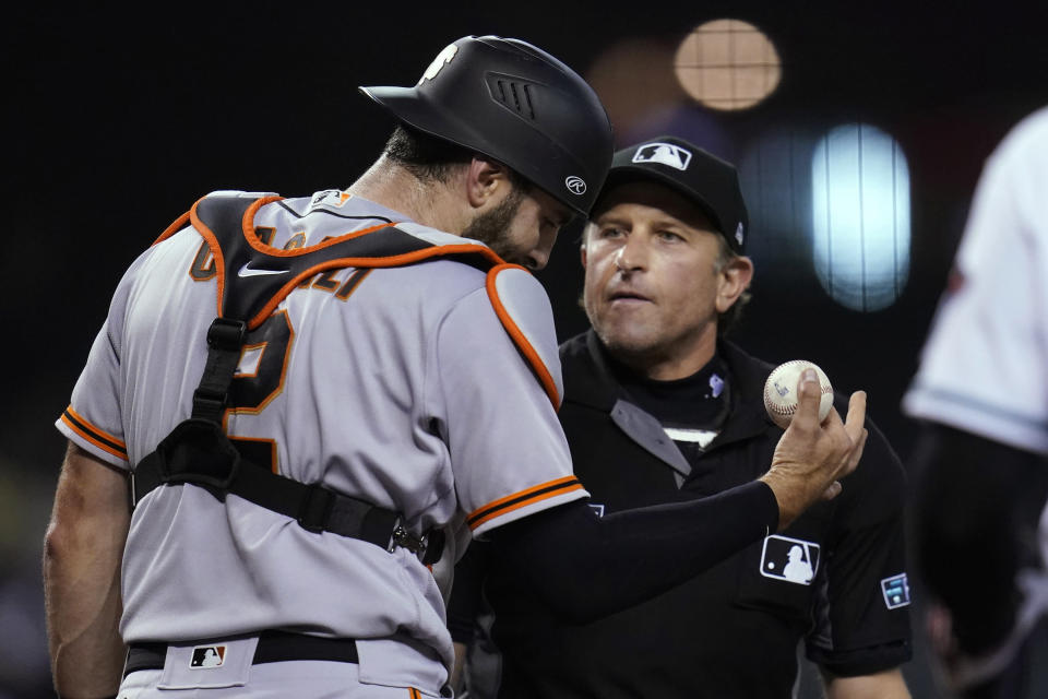 San Francisco Giants catcher Curt Casali, left, argues with umpire Chris Guccione after the umpire called Giants pitcher Johnny Cueto for a balk during the second inning of the team's baseball game against the Arizona Diamondbacks, Tuesday, Aug. 3, 2021, in Phoenix. (AP Photo/Ross D. Franklin)