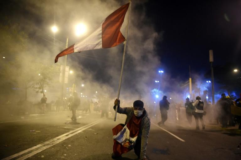 A supporter of ousted Peruvian President Martin Vizcarra holds a Peruvian flag during a protest against the government of interim president Manuel Merino in Lima on November 14, 2020
