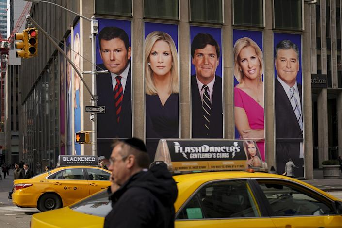 Traffic on Sixth Avenue passes by advertisements featuring Fox News personalities, including Bret Baier, Martha MacCallum, Tucker Carlson, Laura Ingraham, and Sean Hannity: Photo by Drew Angerer/Getty Images