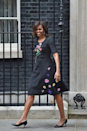 <p>To meet with British Prime Minister David Cameron at Downing Street, Obama wore a three-quarter sleeved black dress with an embroidered bouquet of flowers on the chest and floating petals flowing down the skirt. </p>