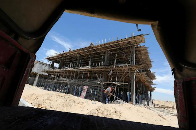 <p>Palestinian workers work on a Qatari-funded construction project in the southern Gaza Strip June 7, 2017. (Photo: Ibraheem Abu Mustafa/Reuters) </p>