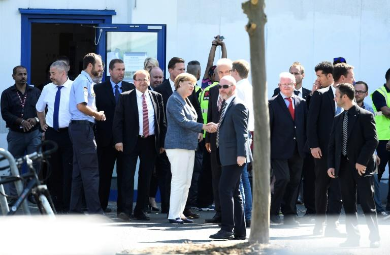 German Chancellor Angela Merkel visits a shelter for asylum-seekers in Heidenau, eastern Germany on August 26, 2015