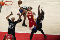 Atlanta Hawks' Trae Young (11) shoots against New York Knicks' Julius Randle (30) and Taj Gibson (67) during the first half in Game 3 of an NBA basketball first-round playoff series Friday, May 28, 2021, in Atlanta. (AP Photo/Brynn Anderson)