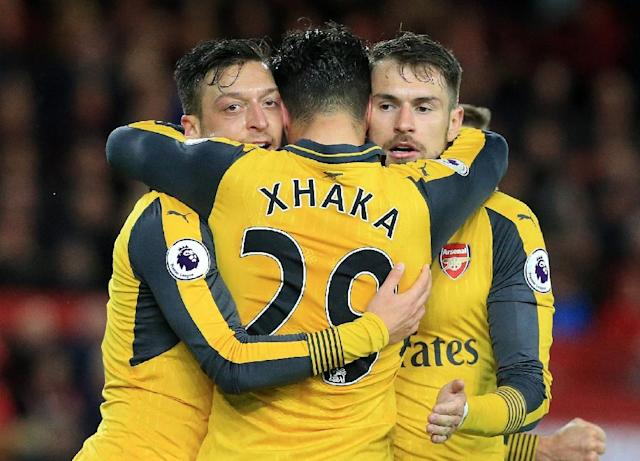 Arsenal's midfielder Mesut Ozil (L) celebrates scoring his team's second goal with Aaron Ramsey (R) and Granit Xhaka (AFP Photo/Lindsey PARNABY)