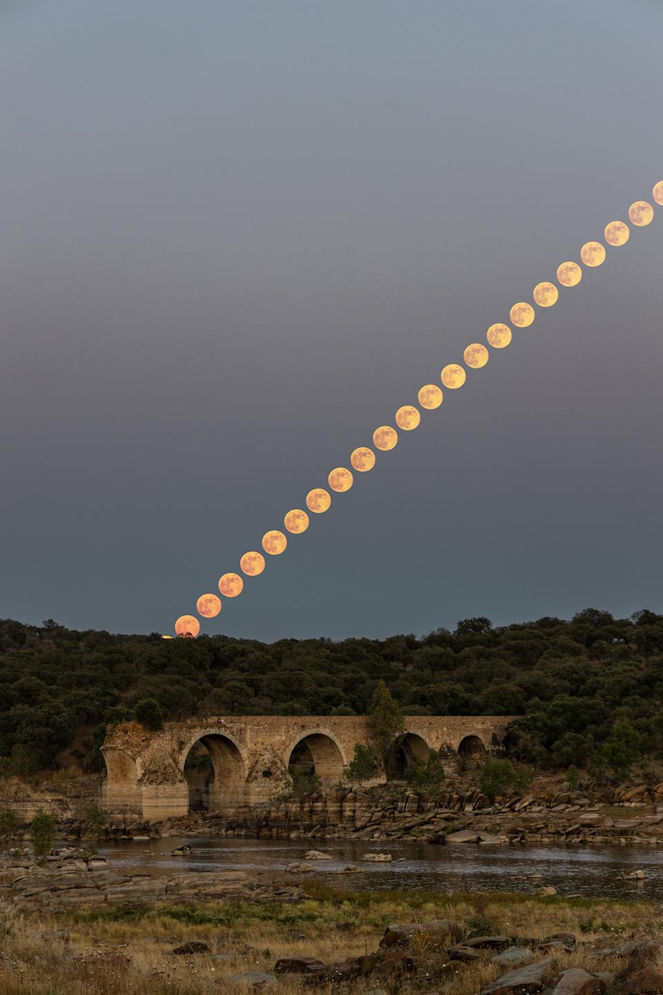 "The Full Strawberry Moon rises over Ponte da Ajuda, a historic bridge near the border between Portugal and Spain, during the penumbral lunar eclipse on Friday (June 5). Astrophotographer Sérgio Conceição created this composite image of the rising moon from Elvas, Portugal, at the end of the eclipse. During this subtle lunar eclipse, the moon passed through the faint outer part of Earth's shadow, known as the penumbra, causing its surface to appear slightly tea-stained. ""It can be seen that the moon was born with a more intense reddish pink color and started to whiten as it rose,"" Conceição told Space.com in an email."