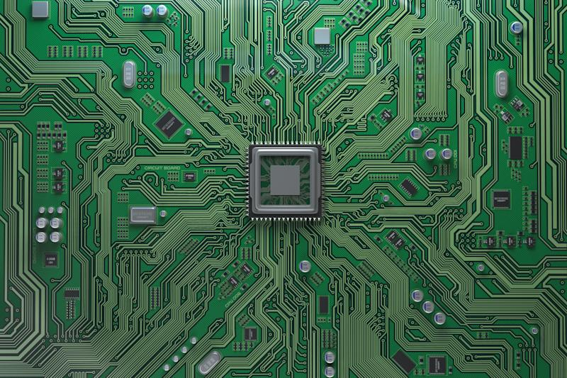A square semiconductor chip in the middle of a green silicon printed circuit board.
