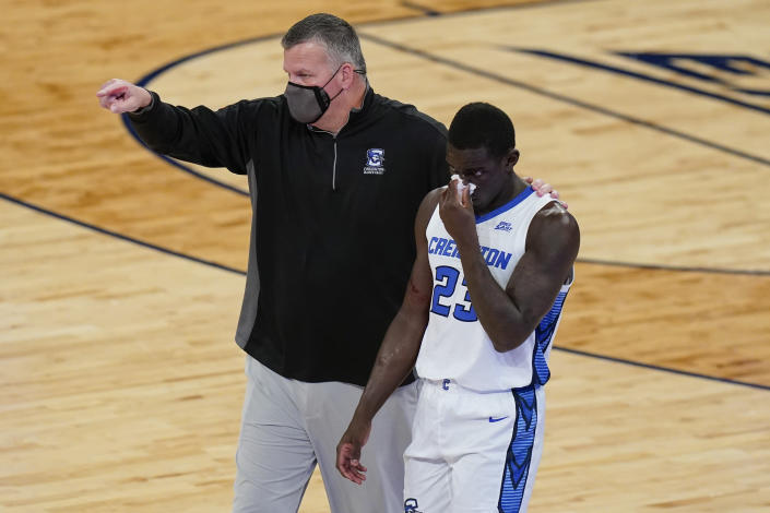Creighton coach Greg McDermott, left, points to the bench as he helps Damien Jefferson (23) after Jefferson was hurt during the first half of the team's NCAA college basketball game against Butler in the Big East men's tournament Thursday, March 11, 2021, in New York. (AP Photo/Frank Franklin II)