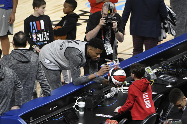 Milwaukee Bucks' Giannis Antetokounmpo signs an autograph during practice at the NBA All-Star basketball game, Saturday, Feb. 15, 2020, in Chicago. (AP Photo/David Banks)