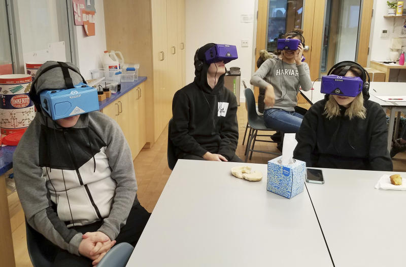 In this Feb. 7, 2018 photo, students at the Berkeley Carroll School in the Brooklyn borough of New York use virtual reality headsets in their classroom. Experts say the technology is still relatively rare in schools, but they expect that to change as costs come down and content improves. Seated at the table from left are Daniel Cornicello, 17, Charlie Hertz, 17, and Taylor Engler, 16. At the table in the back of the room is Angela Aguero, 17. (AP Photo/Deepti Hajela)