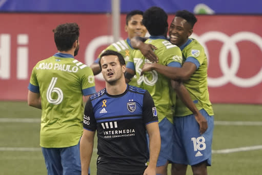 San Jose Earthquakes midfielder Vako, front, walks away as Seattle Sounders defender Kelvin Leerdam, right, celebrates with teammates after scoring a goal during the first half of an MLS soccer match Thursday, Sept. 10, 2020, in Seattle. (AP Photo/Ted S. Warren)