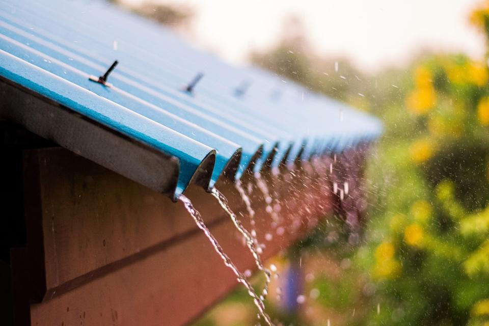 Rain Water Falling From Blue Roof
