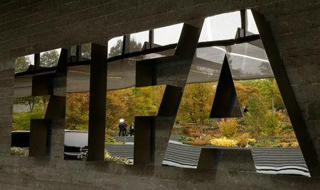 A TV team is reflected in a logo of FIFA at its headquarters in Zurich