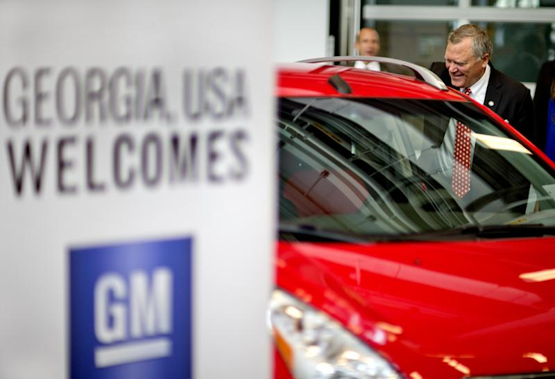 FILE- In this Thursday, Jan. 10, 2013, file photo, Georgia Gov. Nathan Deal, right, looks at a Chevy Spark, an electric vehicle on display at a news conference, in Atlanta.  General Motors said Wednesday, April 24, 2013, that the battery-powered version of its Chevrolet Spark mini-car can travel up to 82 miles on a single charge, putting it among the leaders in mass-market electric vehicles sold in the U.S. (AP Photo/David Goldman)