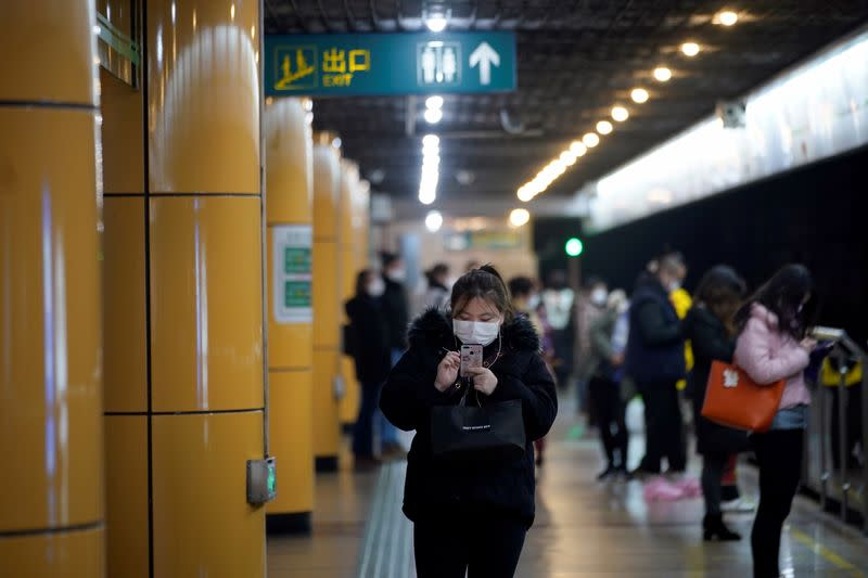 People wear masks as they wait for their train at a subway station in Shanghai