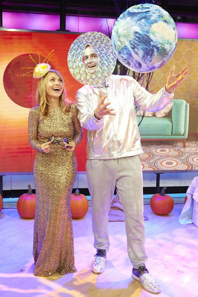 "<p>As seen on <em>Kathie Lee & Hoda</em>! <em>Good Housekeeping</em> Style Director Lori Bergamotto got glammed up in gold to portray the sun and recruited her husband, Nick, to be the moon, occasionally crossing in front of her for full effect.</p><p><strong>What you'll need:</strong> gold sequin dress ($28 and up, <a rel=""nofollow"" href=""https://www.amazon.com/Homecoming-Dress-Formal-Evening-Party/dp/B01FEZ6SAG/ref=sr_1_7?tag=syndication-20"">amazon.com</a>), silver sweat suit ($10, <a rel=""nofollow"" href=""https://www.amazon.com/Silver-Hoodie-Weight-Fitness-Exercise/dp/B00L8KAIC6/ref=sr_1_5?tag=syndication-20"">amazon.com</a>), inflatable Earth ($14, <a rel=""nofollow"" href=""https://www.amazon.com/Earthball-Inflatable-Earth-satellite-images/dp/B005ZI6ZH4/ref=sr_1_3?tag=syndication-20"">amazon.com</a>)</p>"