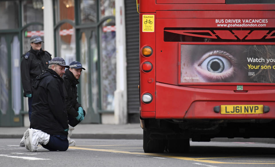Police officers look under a bus as they work at the scene of Sunday's terror stabbing attack in the Streatham area of south London Monday Feb. 3, 2020. Police in London say the man identified as 20-year-old Sudesh Amman was wearing a fake bomb and stabbed two people Sunday before being shot to death by police was recently released from prison, where he was serving for terrorism offenses. (AP Photo/Alberto Pezzali)