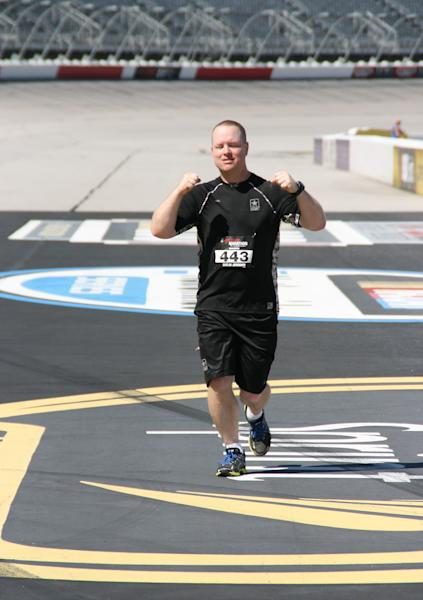 In this photo released by Army Chaplain Paul Hur on Sept. 28, 2013, Army Chaplain Capt. Jeremiah Catlin completes a marathon at the Darlington Raceway, in Darlington, S.C. The Army chaplain is recovered from Stage 4 melanoma and has been declared cancer-free. He says God may have given him the affliction so he could learn to help others who suffer from it. Chaplains Catlin and Hur both attended the Army's Chaplain Center and School at Fort Jackson, S.C. and ran in the race on Sept. 28, 2013. (AP Photo/Susanne M. Schafer)