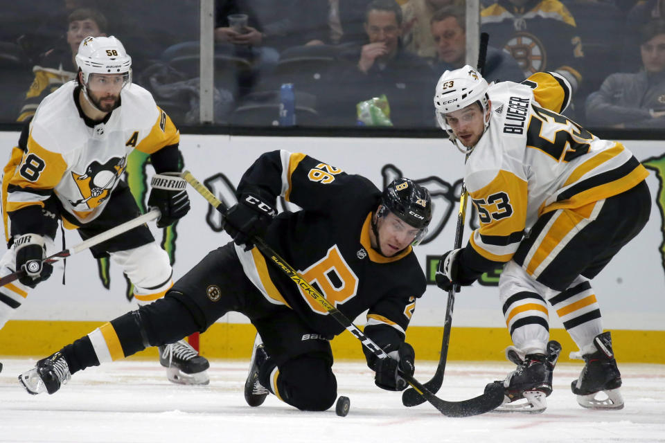 Boston Bruins center Par Lindholm (26) and Pittsburgh Penguins center Teddy Blueger (53) look to make a play for the puck during the third period of an NHL hockey game, Thursday, Jan. 16, 2020, in Boston. (AP Photo/Mary Schwalm)