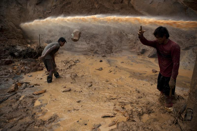 "In this May 3, 2014 photo, a jet stream of water passes above two miners known as ""Maraqueros"" who remove stones and chunks of tree trunks that have been released with the aid of a rustic type of hydraulic jet known locally as a ""Chupadera,"" in La Pampa in Peru's Madre de Dios region. The Chupadera aims powerful jet streams of water at earth walls, releasing the soils that hold the sought after flecks of gold. (AP Photo/Rodrigo Abd)"