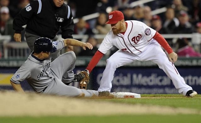 Washington Nationals first baseman Adam LaRoche (25) picks off San Diego Padres' Nick Hundley, left, during the fourth inning of a baseball game, Friday, April 25, 2014, in Washington. (AP Photo/Nick Wass)