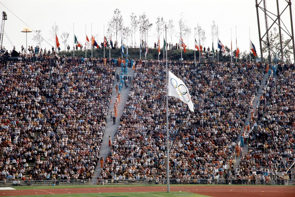 The olympic flag and other national flags fly at half mast in the Munich Olympic stadium on September 06, 1972 during the memorial ceremony for the victims of the hostage-taking of Israeli team members by a Palestinian commando the day before,  during the Munich 1972 Olympic Games. (Getty Images)