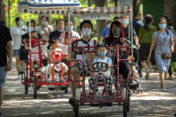 Adults and children ride pedal cycles at a public park in Beijing, Saturday, Aug. 21, 2021. China will now allow couples to have a third child as the country seeks to hold off a demographic crisis that threatens its hopes of increased prosperity and global influence. (AP Photo/Mark Schiefelbein)