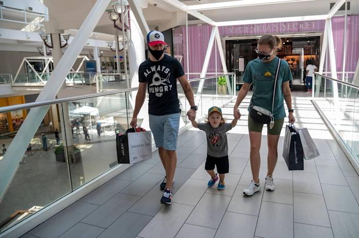 Alex Petrov, left, his son Iaroslav, 3-1/2, and wife Alina shop at Arden Fair mall on Monday, July 13, 2020, the final day of shopping before it temporarily closed again due to rising cases of the coronavirus. Earlier in the day, Gov. Gavin Newsom announced additional closures in the state, including gyms, indoor shopping malls and indoor church worship services.