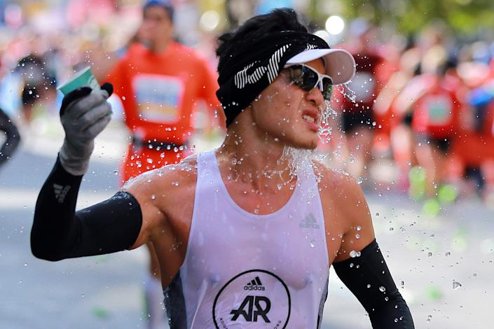 A participant splashes water while running up First Avenue during the 2019 New York City Marathon. (Photo: Gordon Donovan/Yahoo News)
