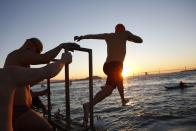A swimmer with the Dolphin Club leaps into San Francisco Bay near Alcatraz Island during the annual New Year's Day swim to Aquatic Park in San Francisco, California January 1, 2015. REUTERS/Stephen Lam (UNITED STATES - Tags: SOCIETY ANNIVERSARY)